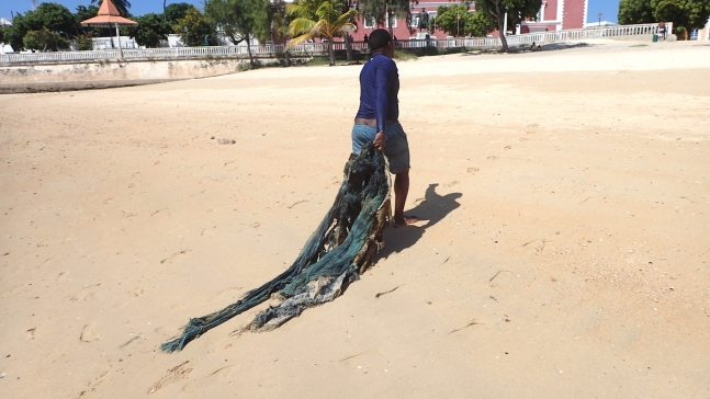 dragging recovered netting up the beach for proper disposal